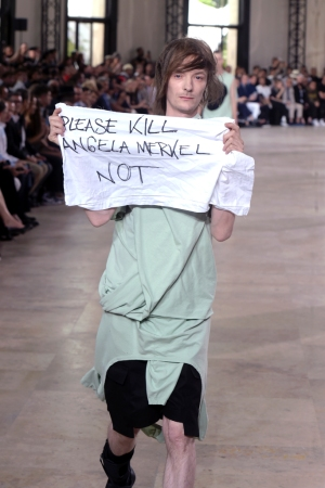Model Jera unfurled a small banner at the Rick Owens Men's Spring 2016 show.