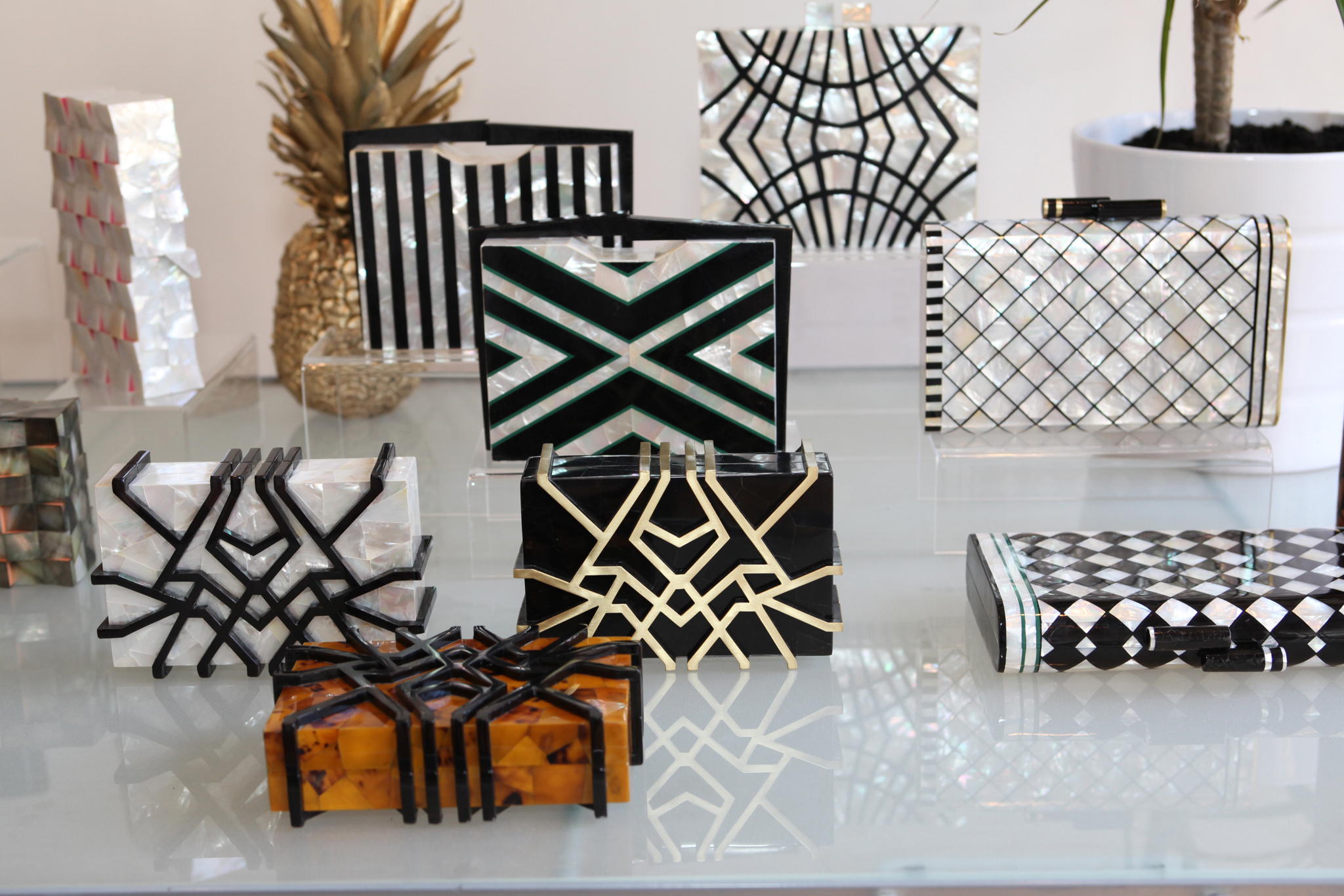 Nathalie Trad stayed true to her architectural, geometric aesthetic while introducing a subtle new motif to her line of clutches for spring.  The designer was inspired by Art Deco design, specifically The Raleigh Miami Beach hotel and its ornately shaped swimming pool, outlined in black tile. Trad interpreted this by adorning her classic mother of pearl bags with patterns in striking black tab shell. — A.D.