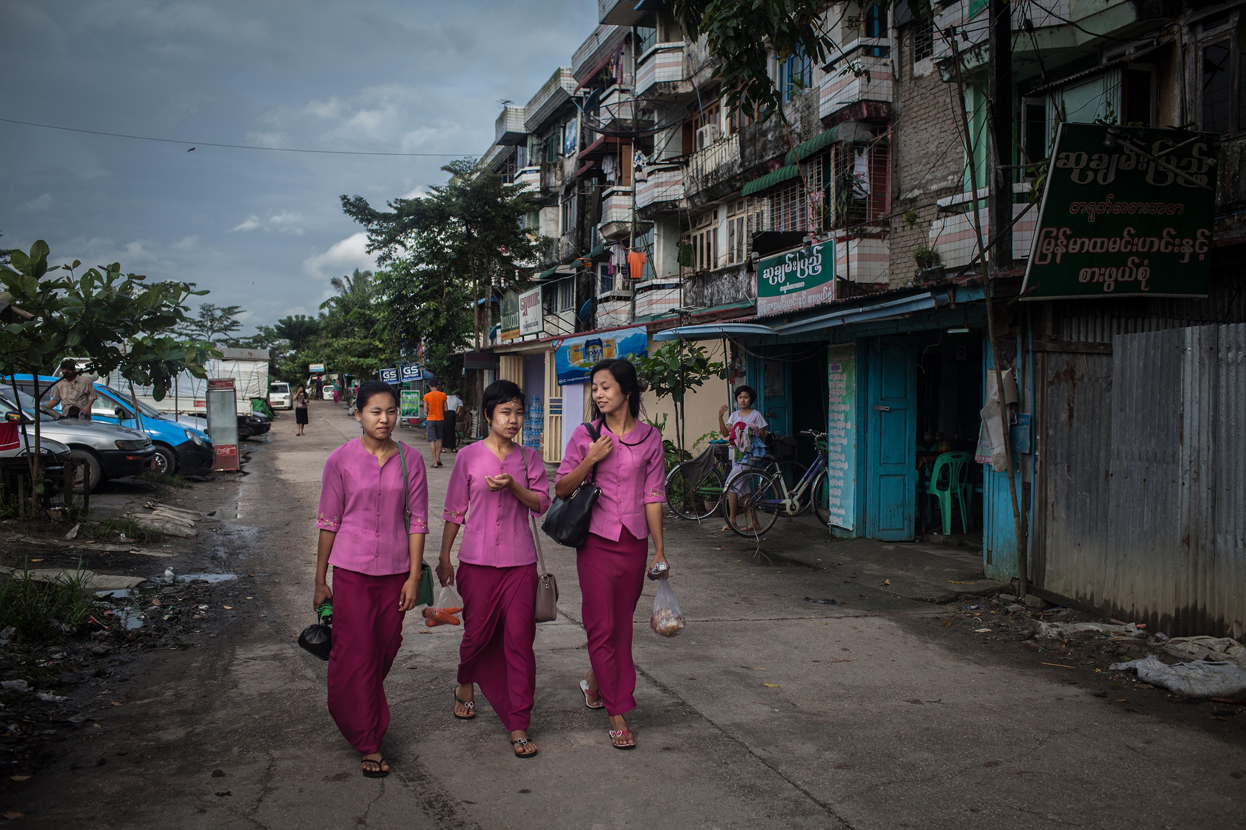 Garment factory workers walk to work from their dormitories on October 13, 2015. On August 29 2015, the government of Myanmar announced a minimum wage of 3,600 kyats (about 3 US$). This slight pay raise was met with hostilities by factory owners in the Garment Industries who either refused to increase pay at all, made layoffs to keep expenses the same or cut overtime pay and benefits. Even those garment factory workers who have seen a increase in their daily wages have seen very little change in their salaries overall.