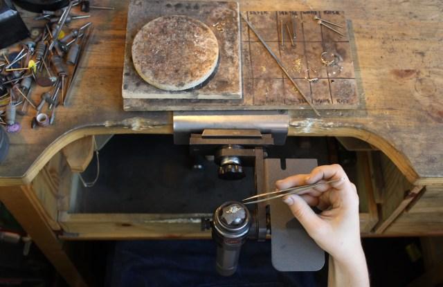 A Catbird jeweler sets a ring.