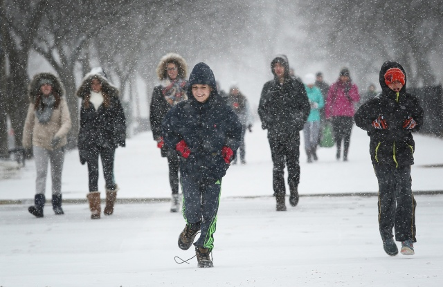 Children run along the National Mall as snow begins to fall in Washington, D.C.