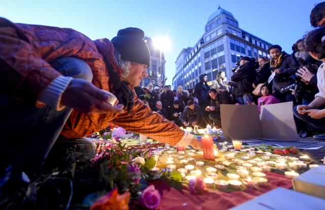People light candles at the Place de la Bourse in Brussels following the attacks.