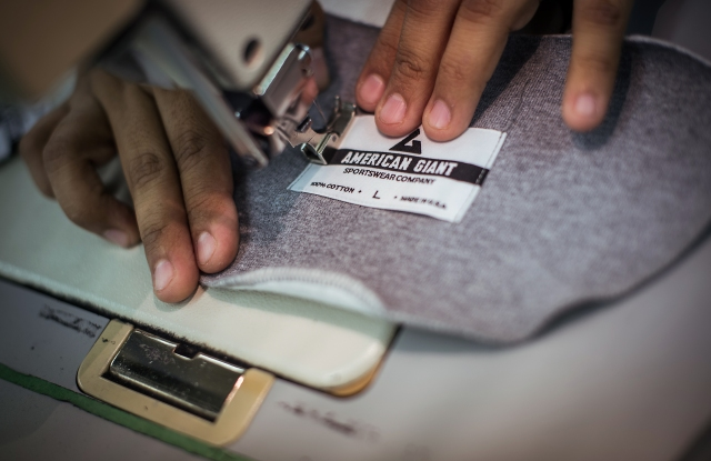 Sewing on the American Giant label.