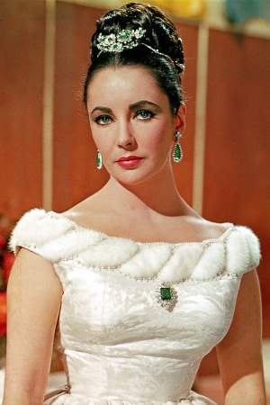 """Elizabeth Taylor in a 1963 publicity still for """"The V.I.P.s"""" wearing her Bulgari platinum, emerald and diamond tremblant brooch, Colombian emerald brooch and matching earrings"""