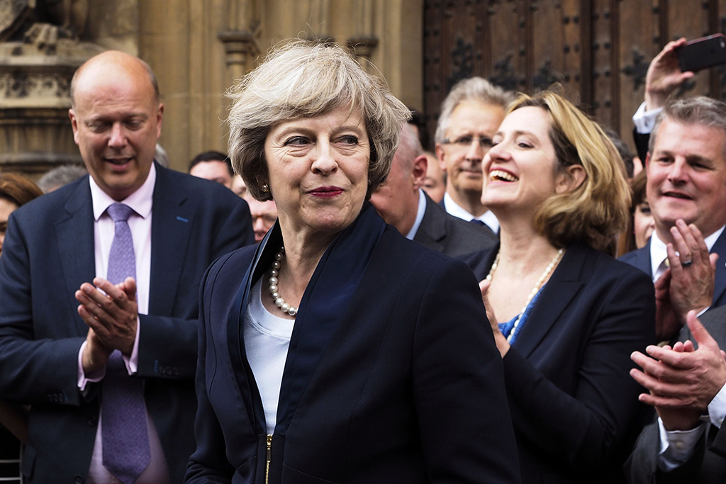 Theresa May is applauded by Conservative Party members of parliament outside the Houses of Parliament in London.