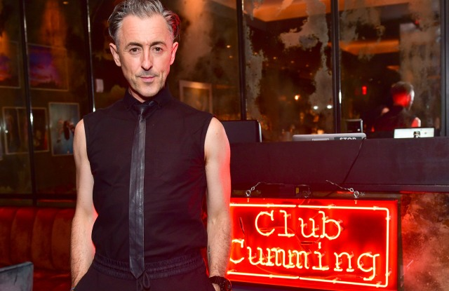 """Alan Cumming pictured with his """"Club Cumming"""" sign."""