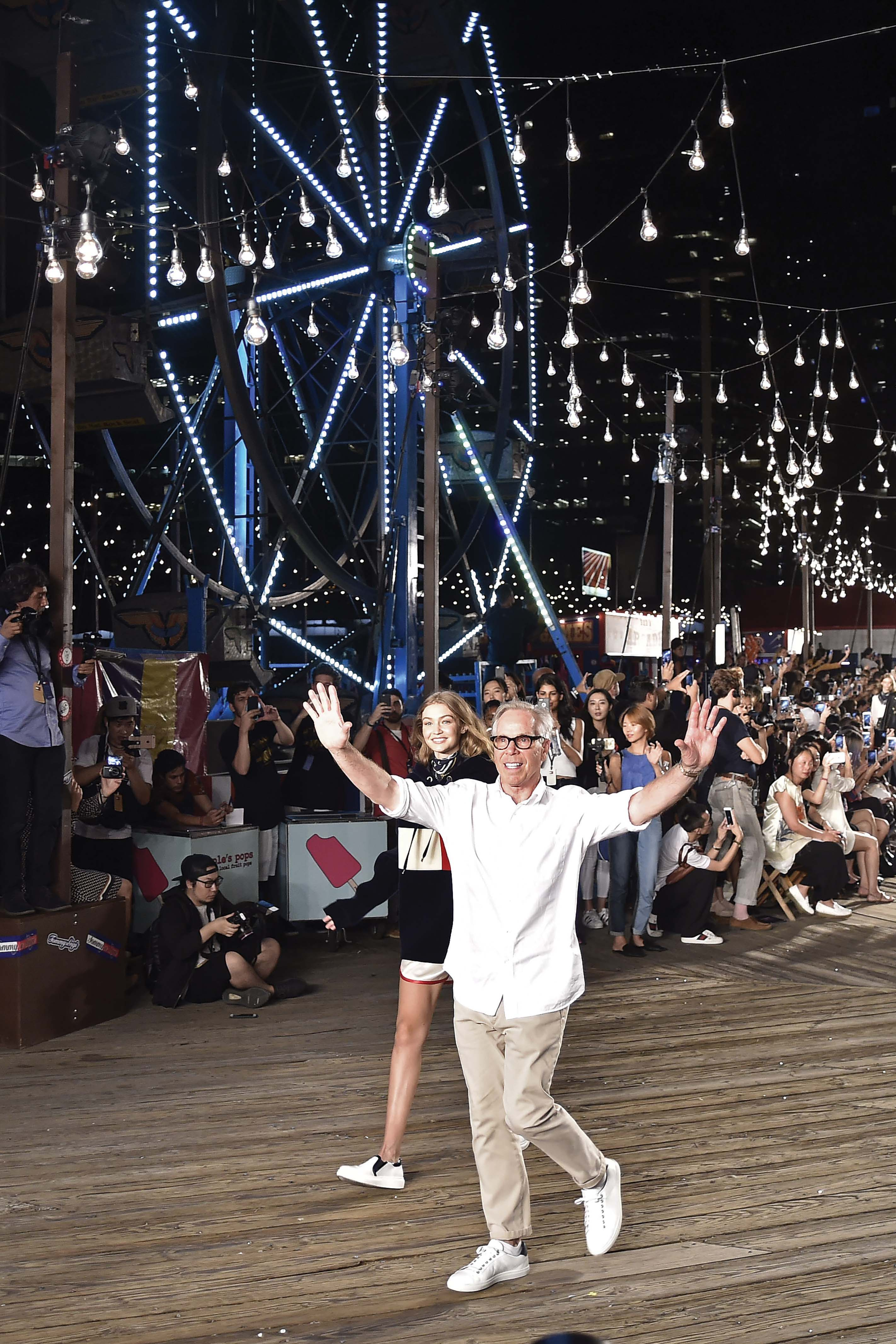 "Tommy Hilfiger thanks the audience at his fall runway ""carnival."""