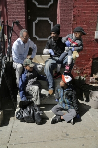 Lester Holt sits on a stoop with neighborhood children while reporting in Baltimore.