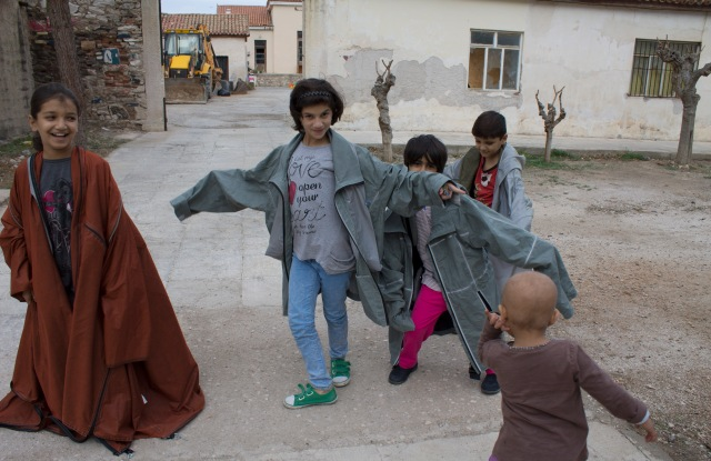 Children in a refugee camp in Greece try on Adiff outerwear.