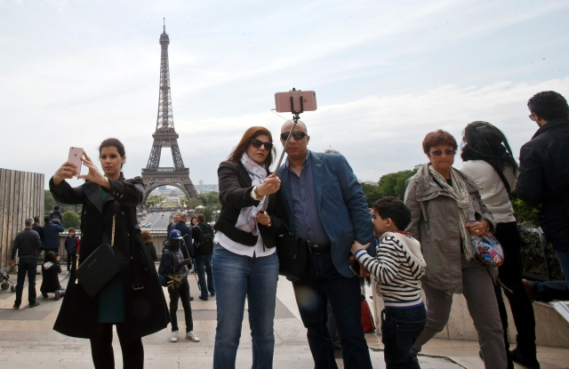 Tourists take selfies at Trocadero Plaza next to the Eiffel tower in Paris.