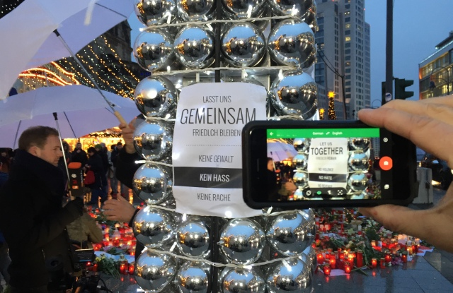 A poster and candles at the crime scene at Breitscheidplatz on the reopening day of the Christmas market