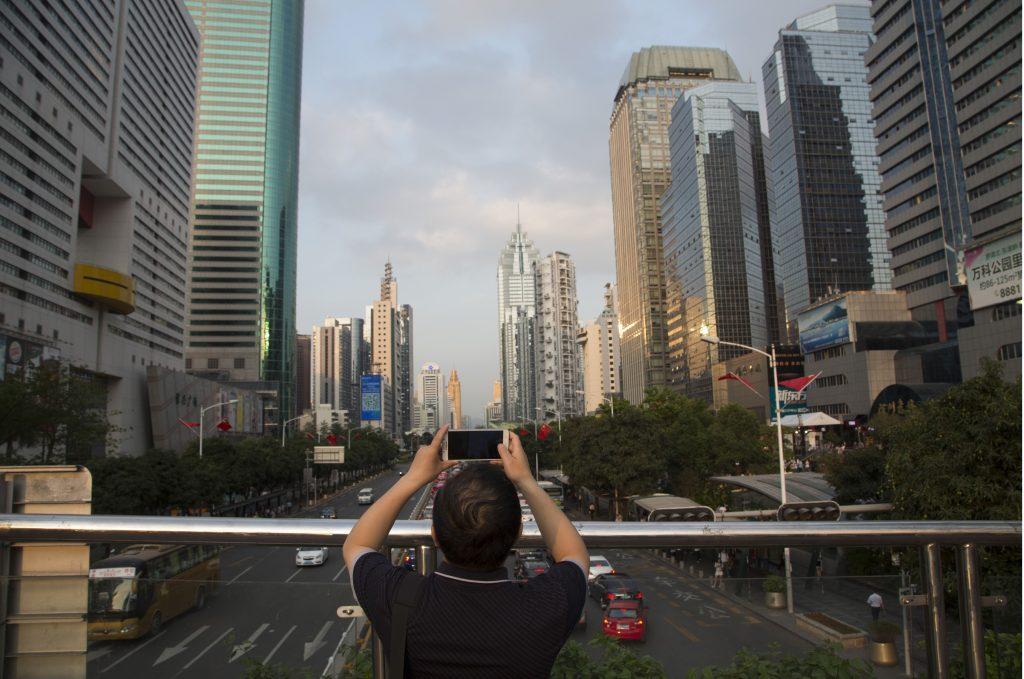 A man takes a photo of downtown Shenzhen.