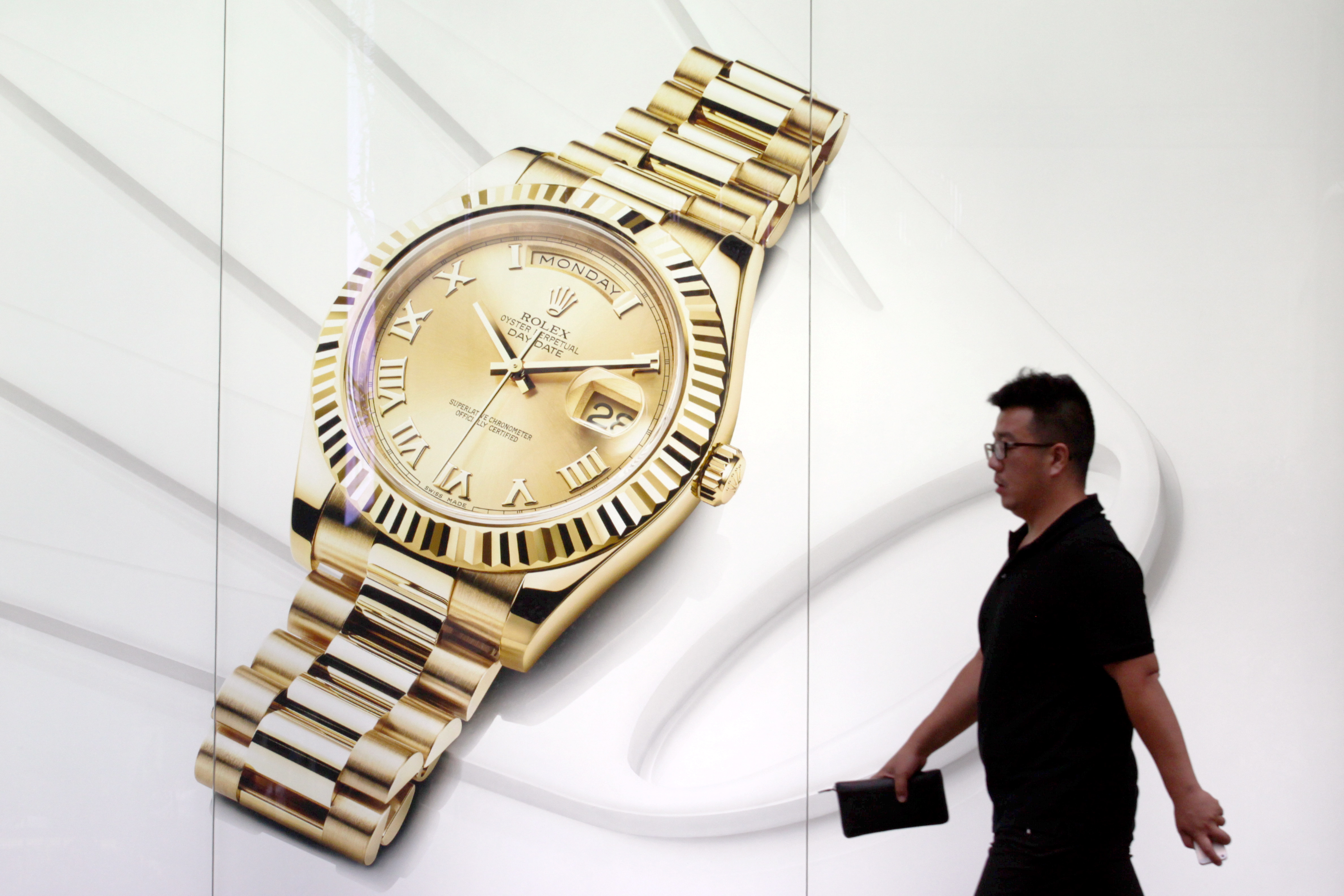 A pedestrian walks past an advertisement for Rolex watches in China.