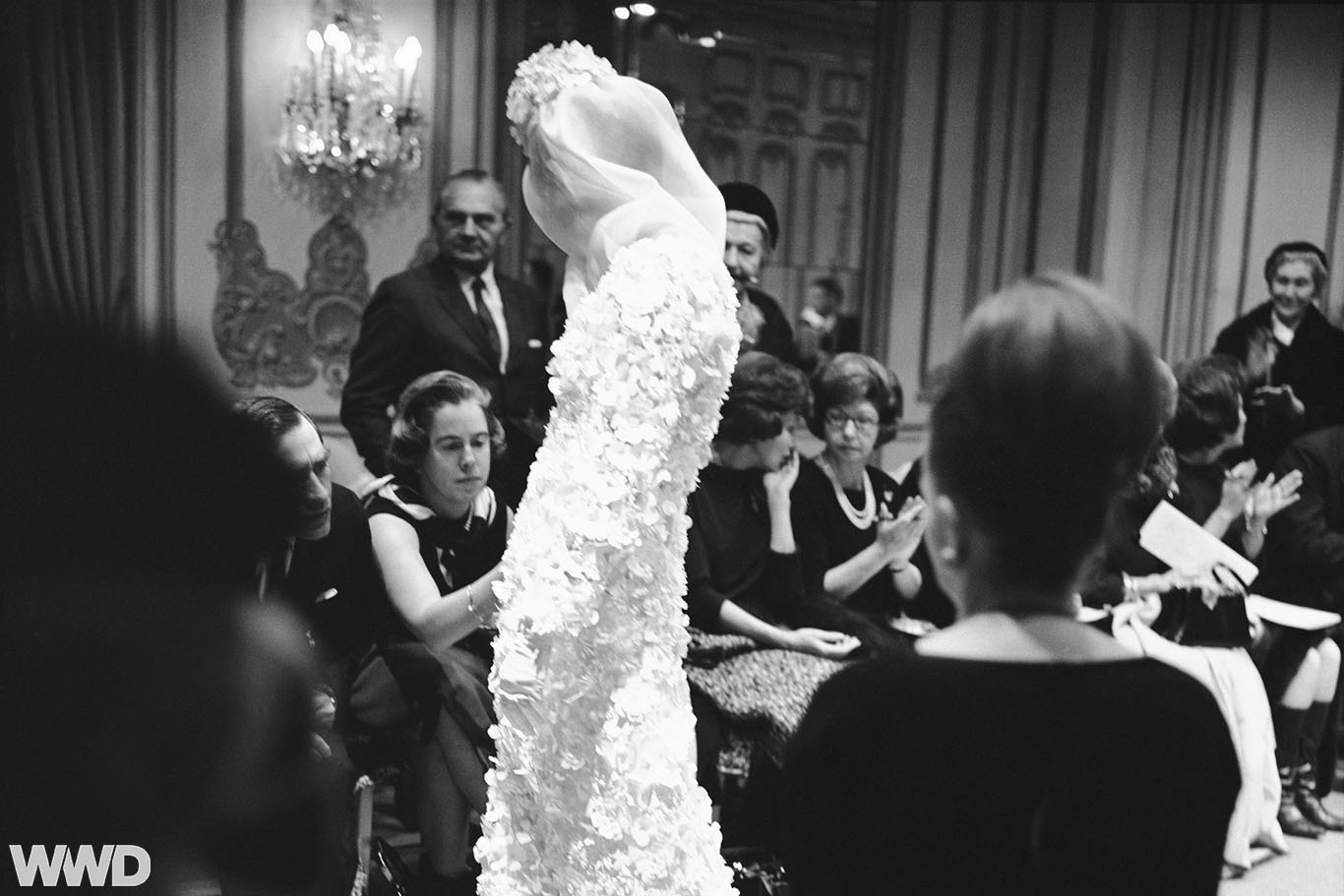 Buyers examine the fabric of a floor-length bridal gown with floral appliqué, veil and headpiece from the James Galanos Couture Spring 1964 collection.