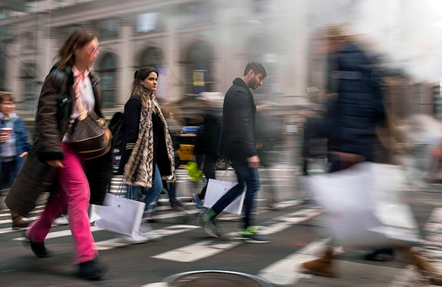Shoppers carry their purchases as they walk though the steam coming from the underground along Fifth Avenue on Black Friday in New York, Friday, Nov. 25, 2016. Shoppers were on the hunt for deals and were at the stores for entertainment Friday as malls opened for what is still one of the busiest days of the year, even as the start of the holiday season edges ever earlier. (AP Photo/Andres Kudacki)