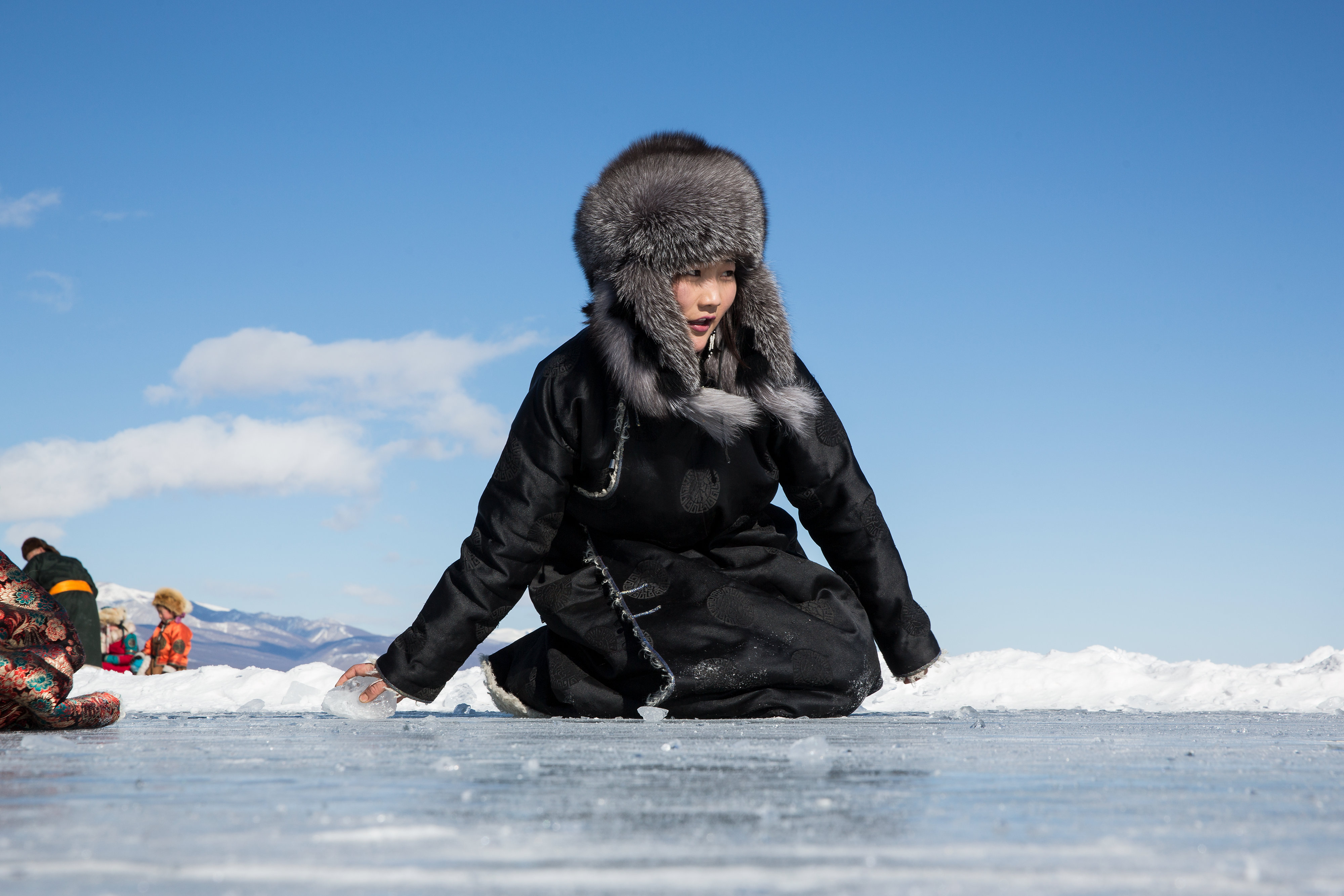 A young Mongolian woman plays a game sliding pieces of ice at the Lake Khovsgol Ice Festival in Khatgal, Mongolia, on March 4, 2017.