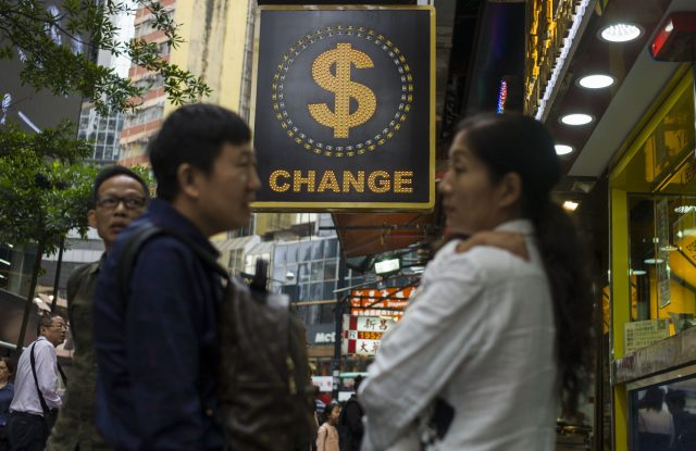 People chat next to a currency exchange shop in Causeway Bay, Hong Kong.