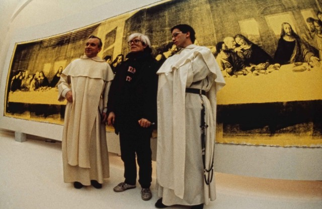 Andy Warhol in front of The Last Supper (Yellow) (1986) at the opening of Andy Warhol – Il Cenacolo at Palazzo delle Stelline, Milan, January 22, 1987.