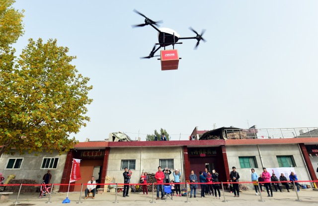 XI'AN, CHINA - NOVEMBER 10:  An unmanned delivery helicopter of JD.com delivers express parcels to villagers on November 10, 2016 in Xi'An, Shaanxi Province of China. It takes the unmanned delivery helicopter about 5 minutes to arrive at the destination, which is 2.3 kilometers away from its starting point. Express parcels are delivered to rural areas around cities in Xi'An by unmanned delivery helicopters, and in this way to improve efficiency and reduce cost.  (Photo by VCG/VCG via Getty Images)