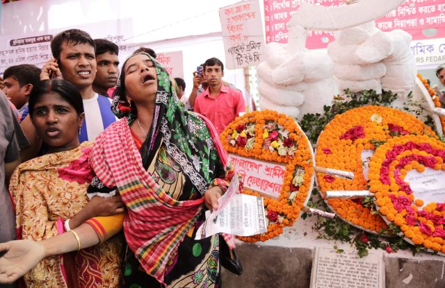 A relative of a Rana Plaza victim cries at a 2016 memorial created for the garment factory workers.