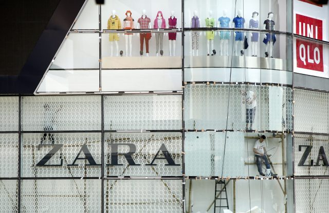 Workers put finishing touches on a Bangkok shopping mall.