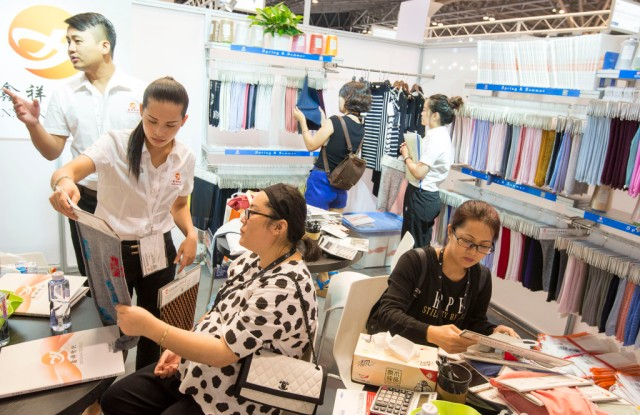 August 29, 2016, Shanghai, China - Vistors examine fabric samples at SPINEXPO fibres, yarn and knitwear trade fair, which was dominated by Chinese exhibitors.