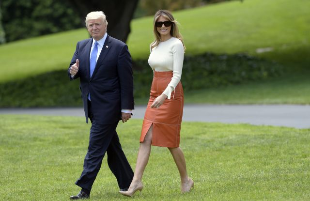 President Donald Trump and first lady Melania Trump walk across the South Lawn of the White House in Washington.