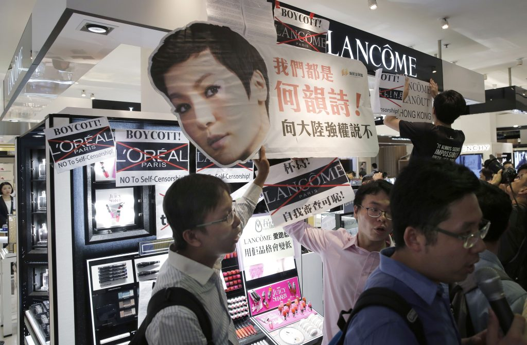 Protestors display protest placards with the picture of Hong Kong singer Denise Ho at a Lancome counter inside a department store at Hong Kong's Times Square.