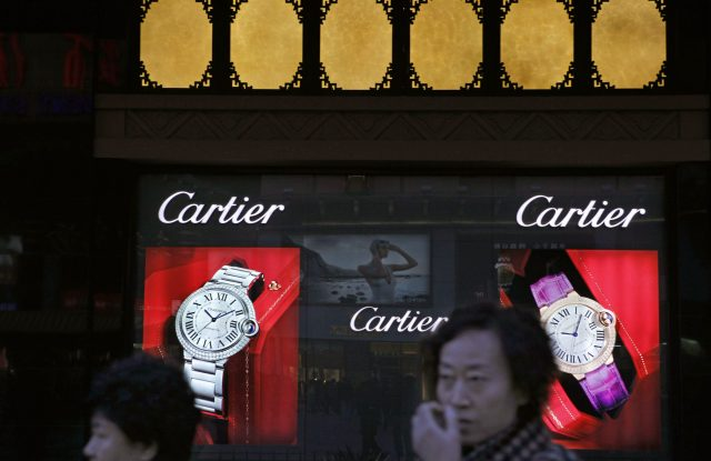 Chinese shoppers walk past a Cartier display in Beijing.