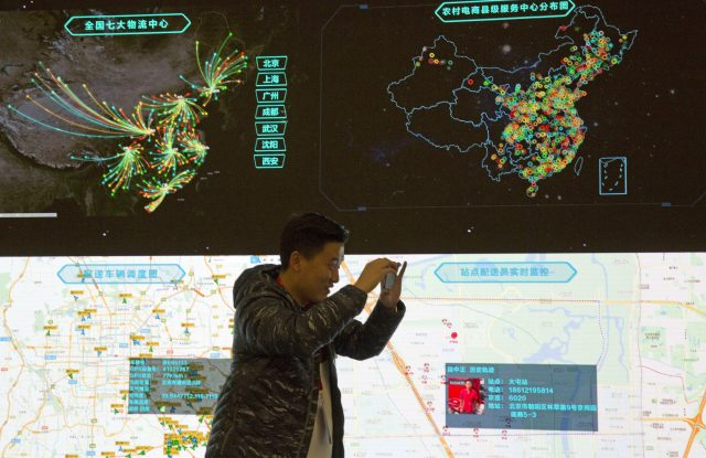 A man takes a photo in front of a display tracking packages across China at JD.com's Beijing command center.
