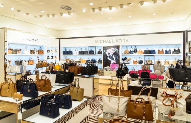 The handbag collection inside a Michael Kors store.