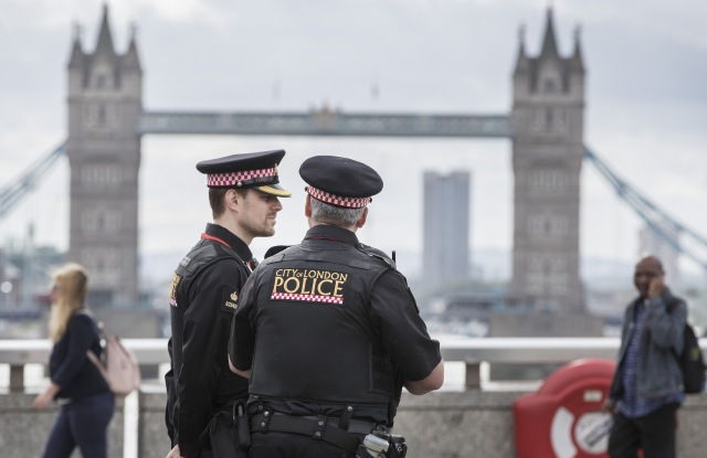 Police watch as people cross London Bridge for the first time after a terrorist attack on Saturday eveningAftermath of London terrorist attack, UK - 05 Jun 2017
