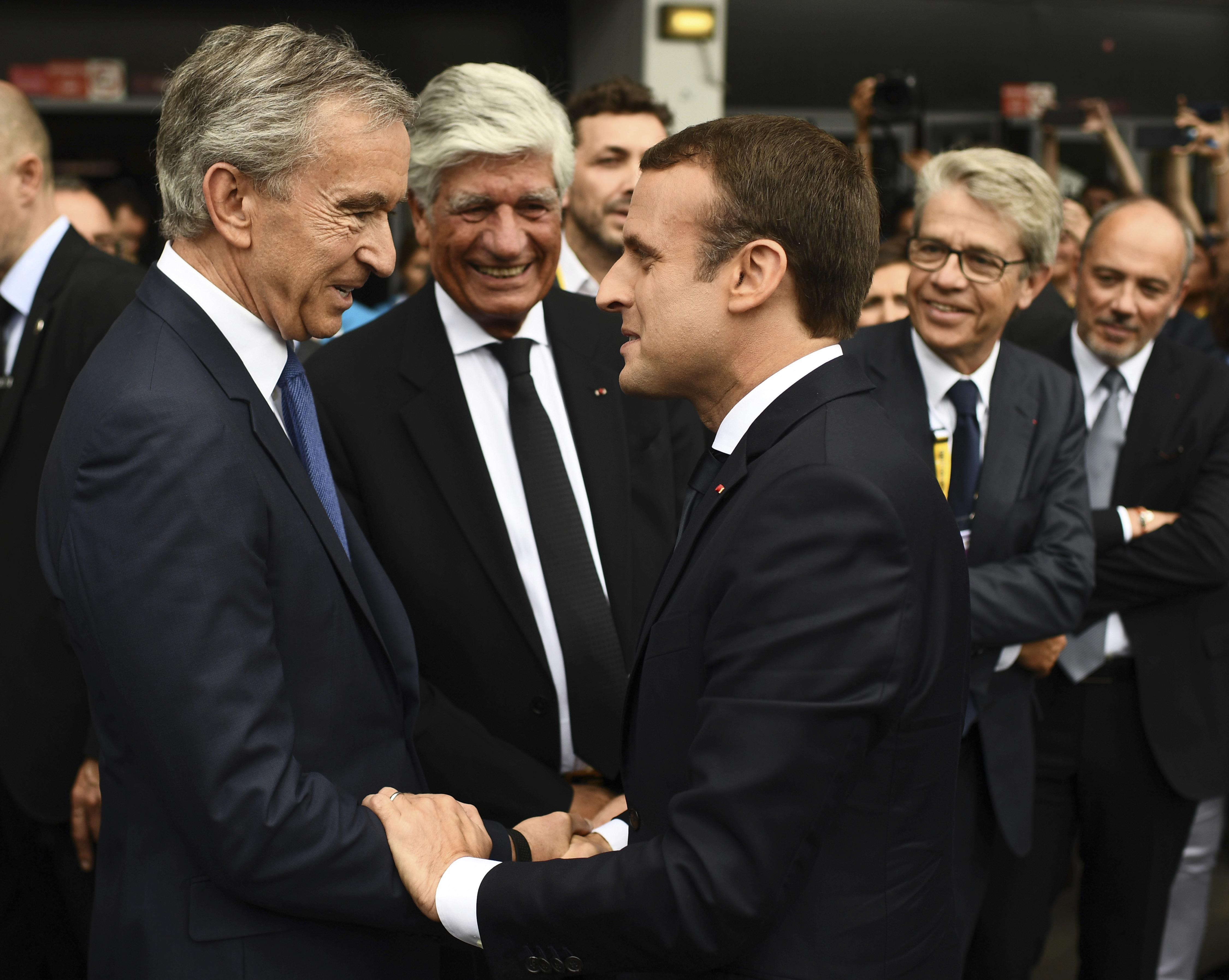 "French President Emmanuel Macron, right, shakes hands with LVMH Group CEO Bernard Arnault as he visits the Vivatech, a gadgets show in Paris, France, Thursday, June 15, 2017. French President Emmanuel Macron is shaking hands with robots and encouraging entrepreneurs as he unveils his strategy to transform the country from a land resting on the laurels of its past into a ""startup nation."" (Martin Bureau/Pool Photo via AP)"