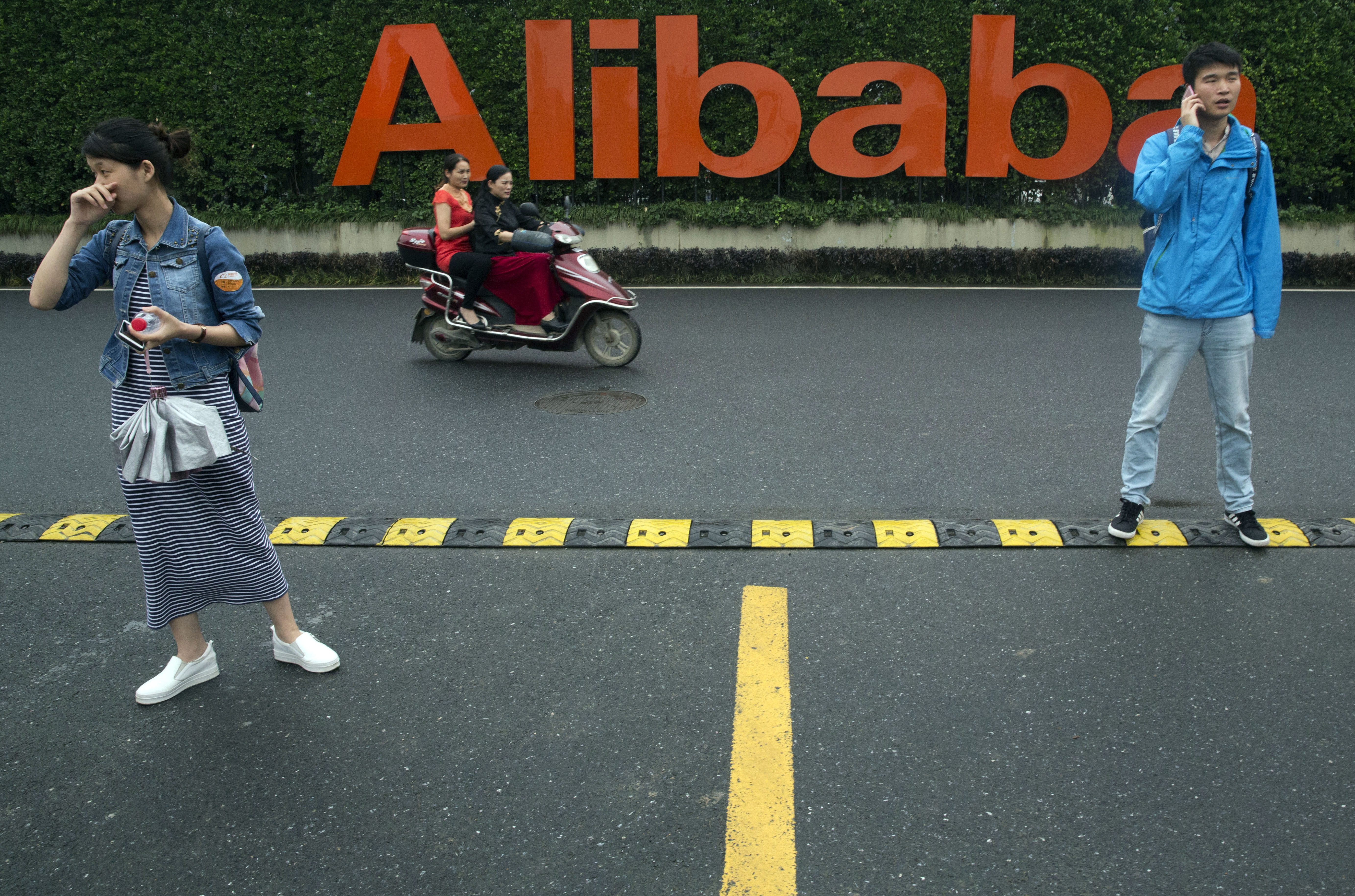 Workers stand near the company logo at the Alibaba Group headquarters in Hangzhou, China.