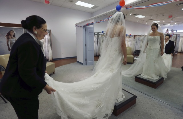 Jo Acchione, Jennifer Dunn Store employee Jo Acchione, left, helps as former Army National Guard member, Jennifer Dunn, tries on a wedding gown at Alfred Angelo Bridal, in Cherry Hill, N.J. The store is offering free wedding dresses to members of the armed services on Veterans Day. The bride to be had to present a valid current military ID or DD214, along with matching government issued photo ID in order to receive the free bridal gownVeterans Day Wedding Dresses, Cherry Hill, USA