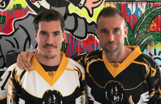 Philipp Plein and Hockey Club Lugano team member Dario Bürgler wearing Plein's jerseys.