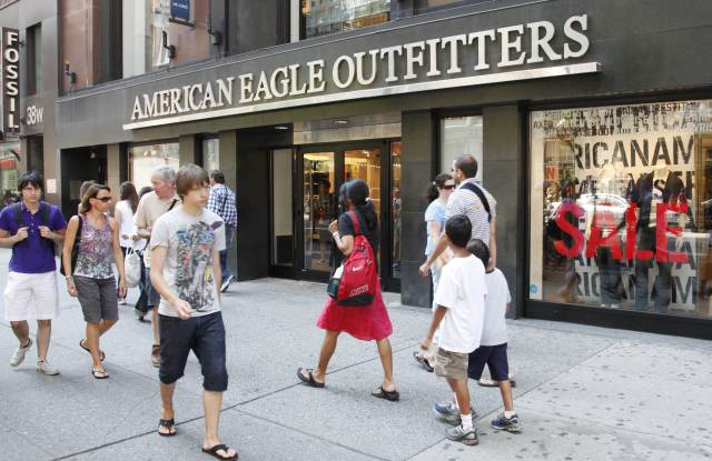 Youngsters pass an American Eagle Outfitters clothing store, in New York. Retail sales managed a modest increase in July after two consecutive declines, but the strength was concentrated in higher sales of autos and gasoline. Most other retailers saw their sales fallEconomy, New York, USA
