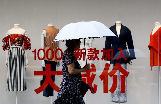 A woman carries an umbrella past a fashion outlet offering its summer sale at a shopping mall in Beijing.