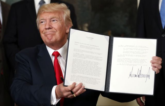 President Donald Trump holds up a signed memorandum calling for a trade investigation of China, in the Diplomatic Reception Room of the White House in WashingtonTrump, Washington, USA - 14 Aug 2017