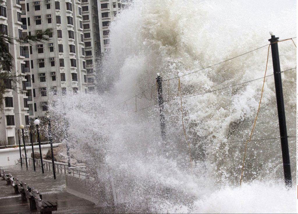 Large waves crash against a sea wall by a housing estate in Hong Kong.