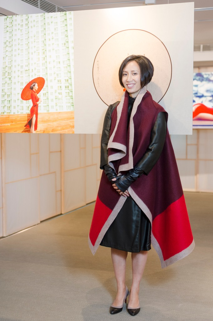 Jiang Qiong Er poses in front of a photograph of by Chen Man.