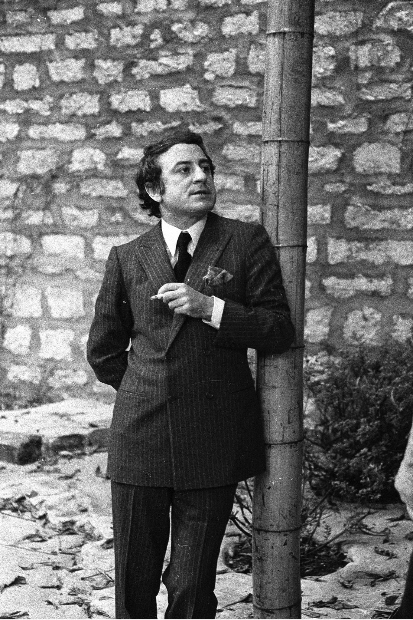 Pierre BergŽ  talking in the garden of Yves Saint Laurent's Paris home.