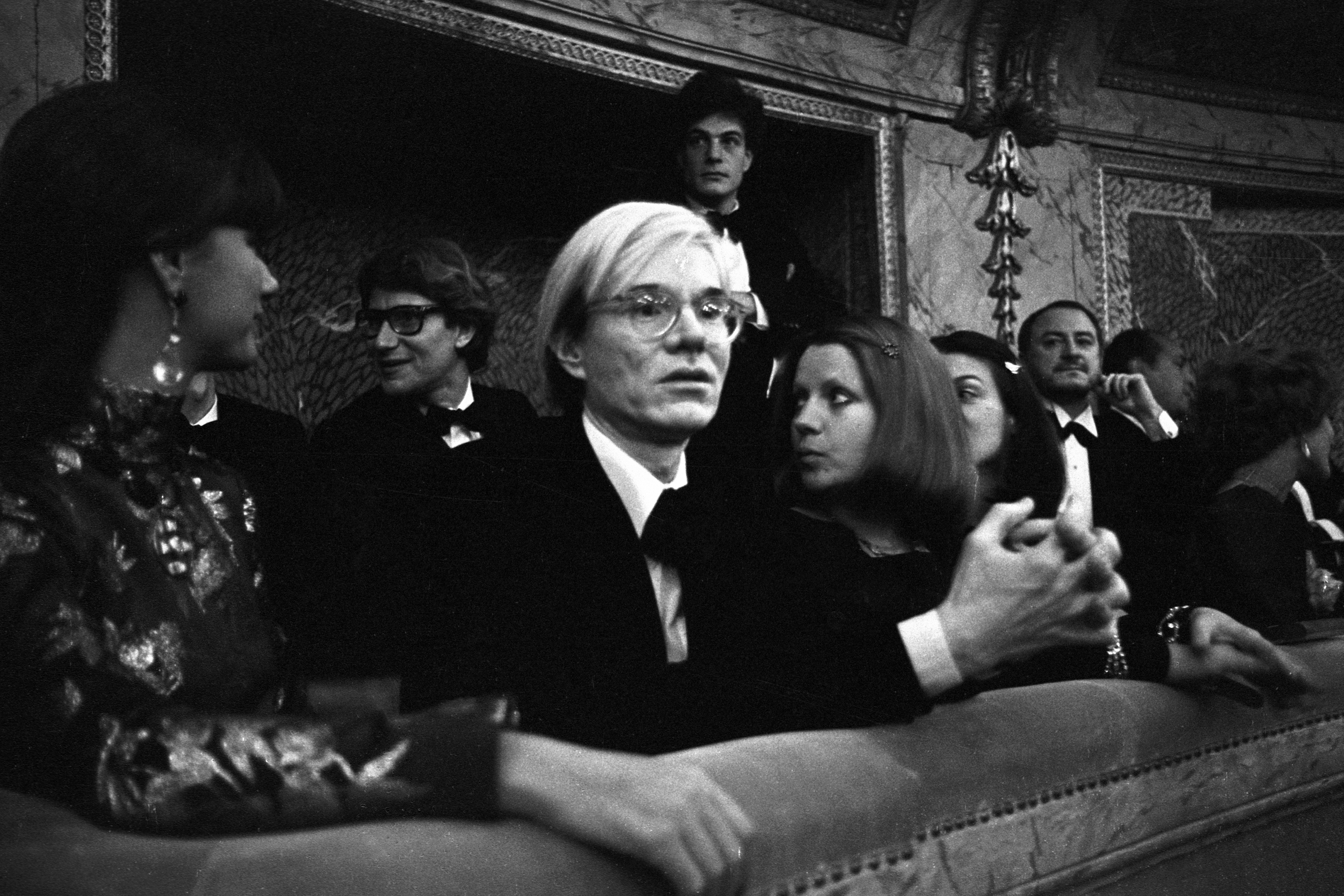 Andy Warhol, Yves Saint Laurent, Mary Russell and Pierre Berge during the fashion show to benefit the restoration of the Chateau of Versailles, on November 28, 1973 in Versailles,