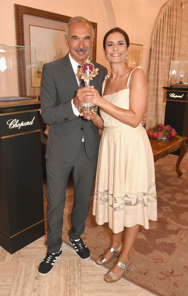 VENICE, ITALY - SEPTEMBER 01: Carlo Capasa and Livia Firth pose with the Green Carpet Fashion Award as they attend an intimate lunch to announce Chopard as partner for The Green Carpet Fashion Awards at Hotel Cipriani on September 1, 2017 in Venice, Italy. (Photo by David M. Benett/Getty Images for Eco-Age)