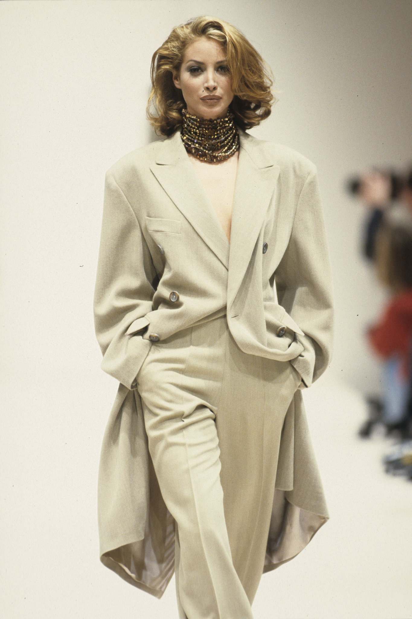Christy Turlington wears an off-white suit with a knee-length jacket and beaded choker on the runway for designer Jil Sander's Fall 1992 show in Milan