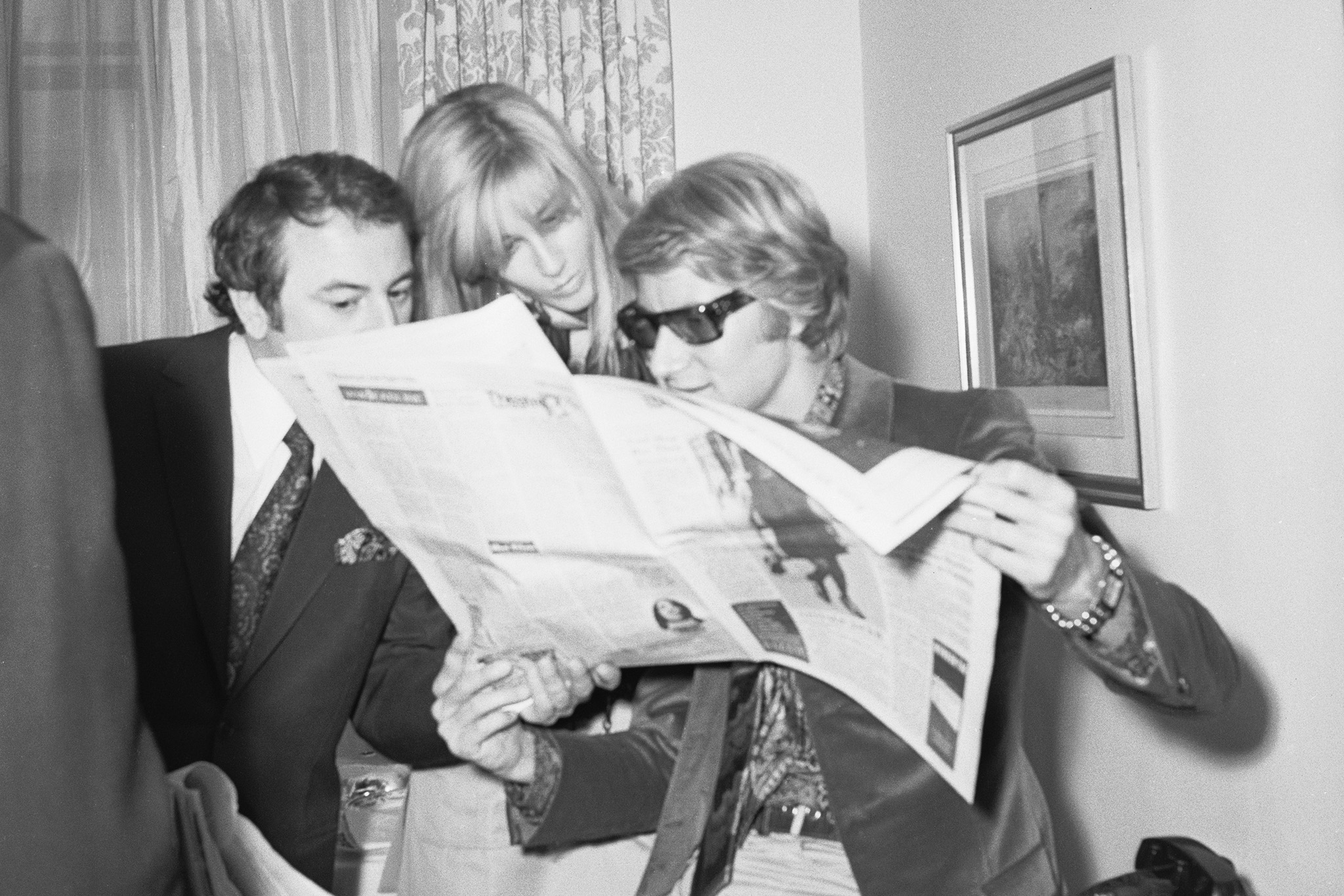 Yves Saint Laurent reading Women's Wear Daily with Pierre Berge and model Betty Catroux after arriving in New York prior to attending a party given by Andy Warhol at the downtown Factory location.