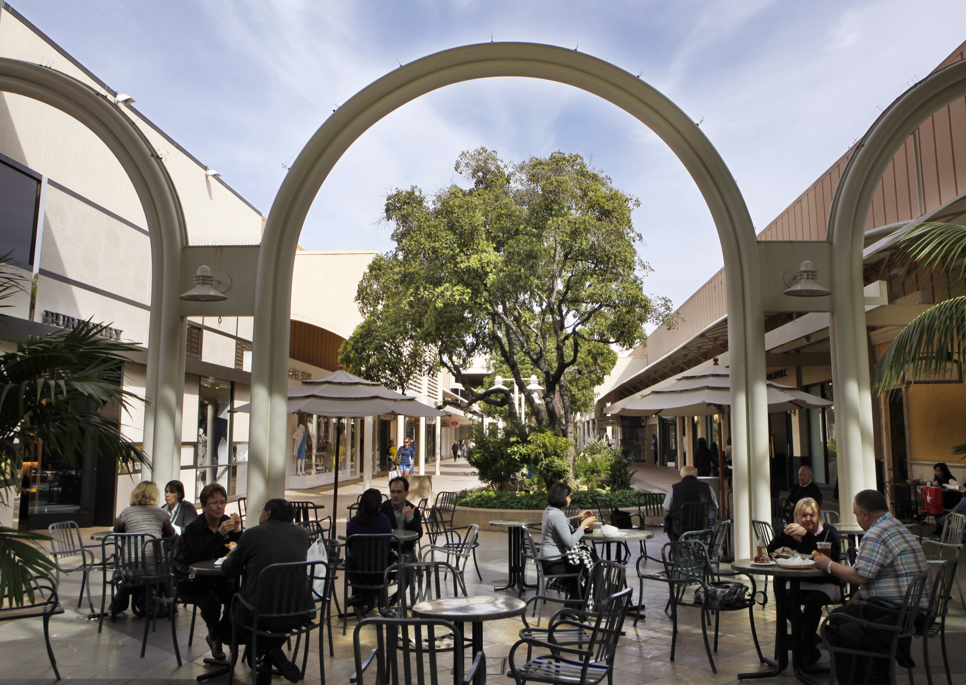 People sit at tables at the Stanford Shopping Center, a Simon Property Group property in Palo Alto, Calif., . Simon Property Group, the nation's largest shopping mall owner, made a $10 billion hostile bid Tuesday to acquire ailing rival General Growth PropertiesSimon Properties General Growth, Palo Alto, USA
