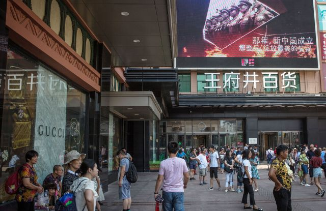 Chinese people walk next to a screen showing Chinese soldiers, at a shopping and tourist district in Beijing, China, 30 July 2017. China will mark the 90th anniversary of the founding of the People's Liberation Army on 01 August 2017.Daily life in Beijing, at 90th anniversary of the founding of the People's Liberation Army, China - 30 Jul 2017