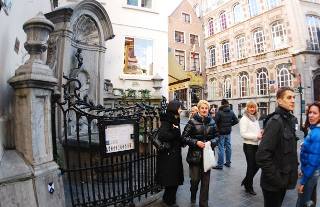 Tourists taking photographs of the famous Manneken Pis statue in Marols area of Brussels. Designed by Jerome Duquesnoy and put in place in 1618, the small bronze statue depicts a naked little boy urinating into the fountain's basin. Brussels, Belgium.Brussels, Belgium - Mar 2011