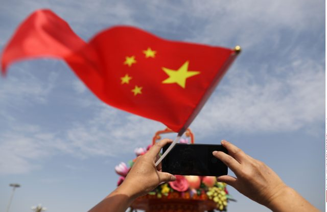 A Chinese tourist holds a Chinese national flag and uses their mobile phone to take a photograph in Tiananmen Square during National Day celebrations in Beijing, China, 01 October 2017. China celebrates its National Day on 01 October, marking its 68th founding anniversary.National Day celebrations in Beijing, China - 01 Oct 2017